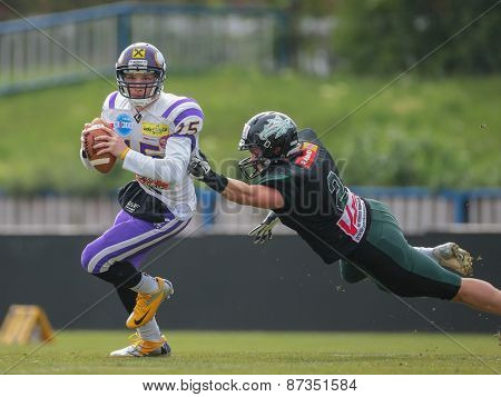 VIENNA, AUSTRIA - APRIL 13, 2014: QB Alexander Thury (#15 Vikings) is tackled by LB Nikolaus Stieldorf (#2 Dragons).