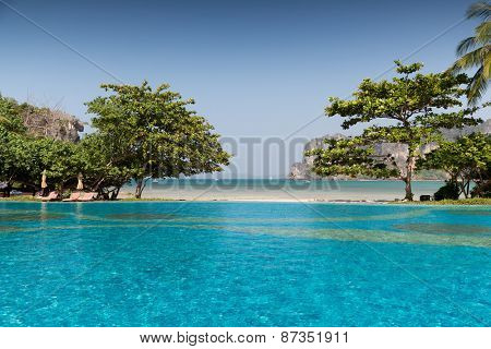 summer holidays, tourism, travel and leisure concept - swimming pool at thailand touristic resort beach