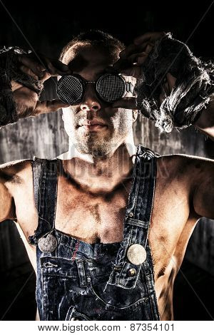 Close-up portrait of a strong muscular man coal miner standing over dark grunge background. Mining industry. Art concept.