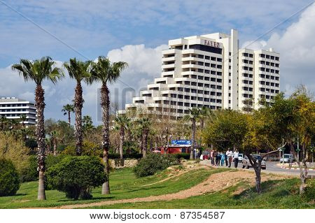 ANTALYA, TURKEY - MARCH 26, 2014: People strolling against the Ozkaymak Falez hotel. This 5 star hotel offers to his guests 342 rooms, spa complex, pools and other facilities