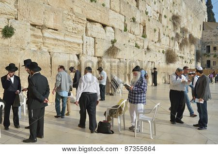 JERUSALEM, ISRAEL - MARCH 20, 2014: Jews pray under the Western Wall in the Old city. The Old City is listed as UNESCO World Heritage site since 1981