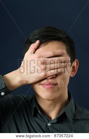 Young Asian man showing facepalm