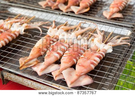 cooking, asian kitchen, sale and food concept - grilled squids at street market