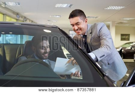 auto business, sale and people concept - happy man with dealer buying car in auto show or salon