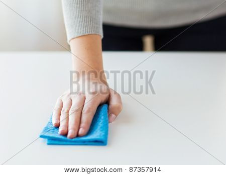 people, housework and housekeeping concept - close up of woman hand cleaning table with cloth at home