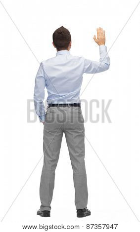 business, people, gesture and office concept - businessman waving hand or touching something imaginary from back
