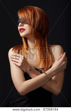 Portrait of red-haired submissive in handcuffs