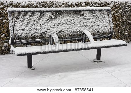 Snow covered empty bench