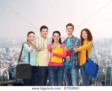 friendship, education and people concept - group of smiling teenagers with folders and school bags showing thumbs up over city background