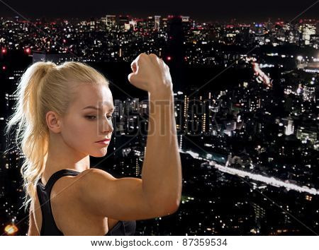 fitness and diet concept - close up of beautiful athletic woman flexing her biceps