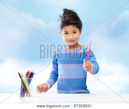 children, creativity and happy people concept - happy little girl drawing with coloring pencils over blue sky background