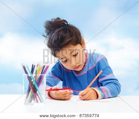children, hobby, childhood and happy people concept - little girl drawing over blue sky background