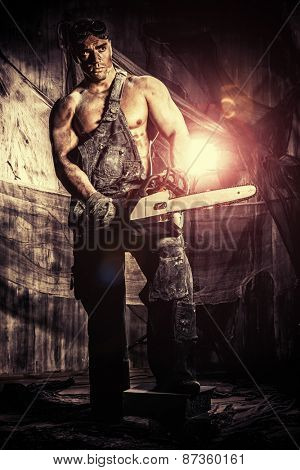 Handsome muscular man with a chainsaw over dark grunge background.