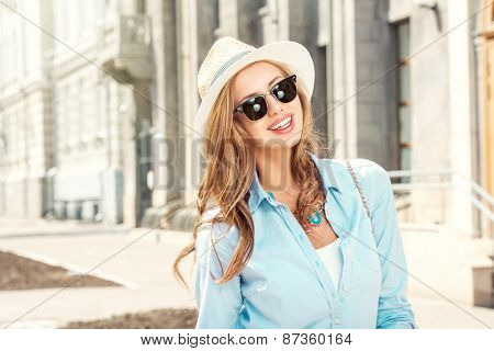 Beautiful young woman walking in the city. Fashion.