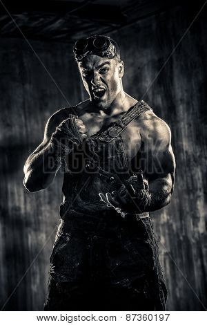 Brutal muscular dirty man expressing aggression over dark grunge background. Mining industry. World of the future, Apocalypse. Sepia.