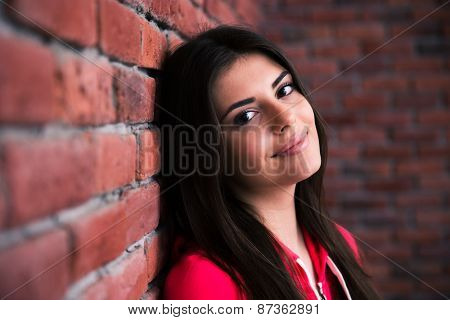 Closeup portrait of a happy woman leaning on the brick wall
