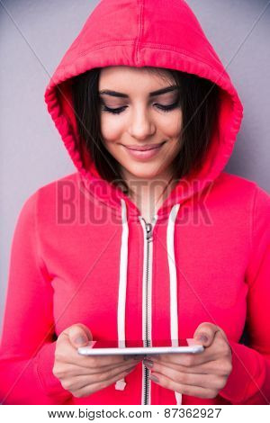 Closeup portrait of a happy young woman using smartphone. Wearing in pink sports jacket. Looking on smartphone