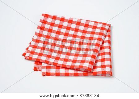 close up of red and white checkered napkin on white background