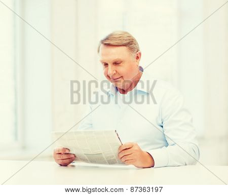 oldness, news, leisure and happiness concept - old man at home reading newspaper