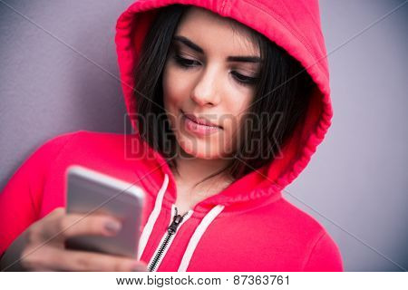 Closeup portrait of a young beautiful woman with smartphone over gray background