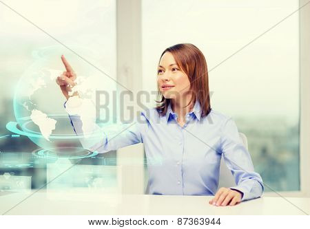 business, education and technology concept - smiling woman pointing to earth hologram