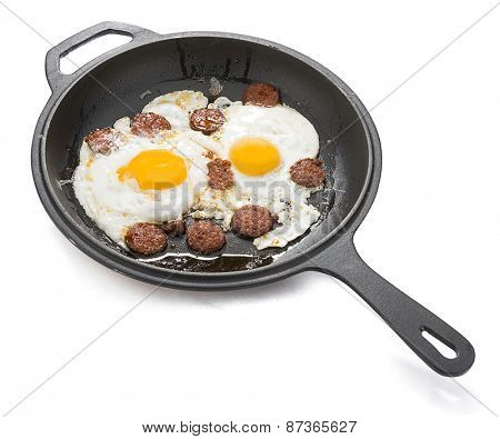 Turkish sausage with egg called sucuklu yumurta on iron cast pan isolated on white background.