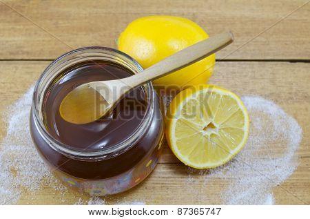 Jar Of Dark Honey A Wooden Spoon And Lemons