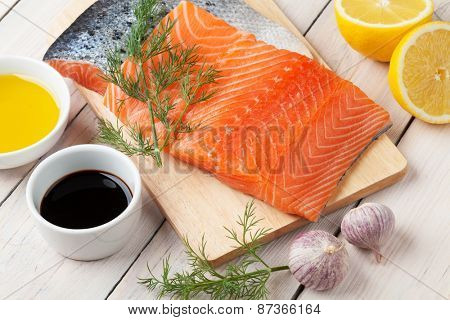Salmon, spices and condiments on wooden table