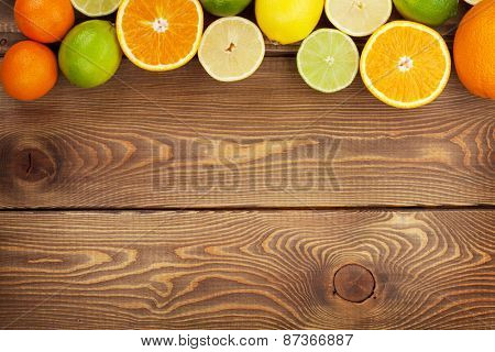 Citrus fruits. Oranges, limes and lemons. Over wooden table background with copy space