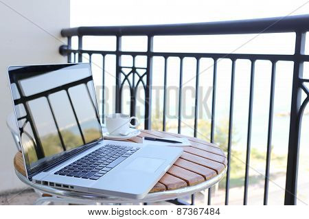 Computer Laptop On Balcony With Sea View And Coffee