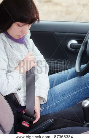 Woman putting on a seatbelt for safety