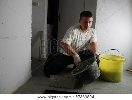 Handyman Working With Spatula To Laying Floor With Stone Plates