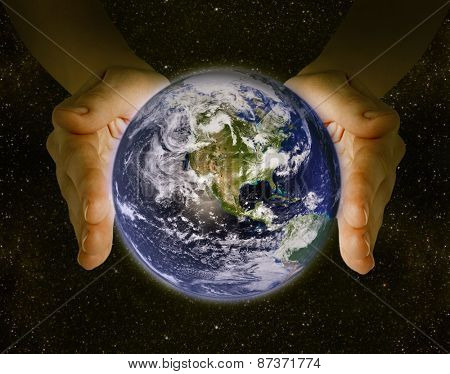 man holding the planet earth in the hands against the background of the galaxy.