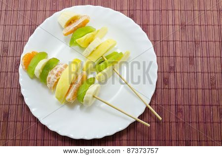 Delicious Fruit Skewers On A White Plate