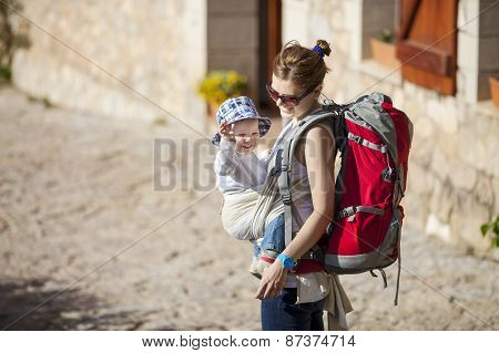 Woman tourist carrying her little son in sling