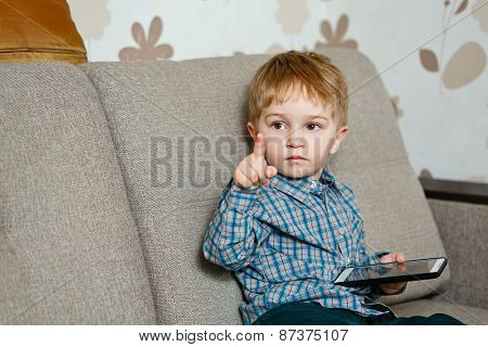 Boy Sitting On A Sofa With A Smartphone