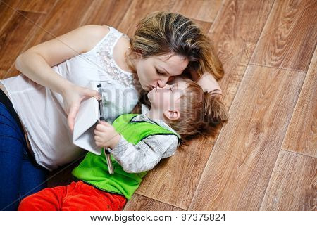 Mom And Son Playing With Tablet Pc While Lying On The Floor