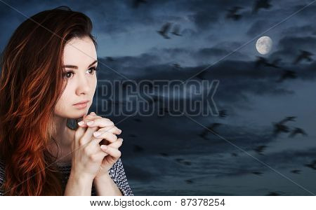 Praying Woman Against Cloudy Sky With Moon
