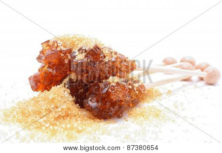 Brown sugar crystal on wooden stick and brown granulated sugar