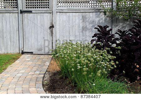 Pretty landscaped yard with walkway and gray gate