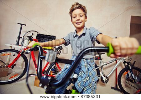 Adolescent boy in casualwear sitting on bicycle