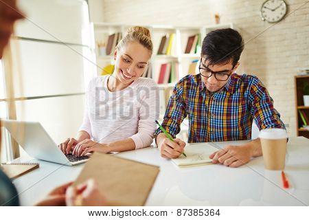 Teenage guy drawing in library while happy girl looking at his picture