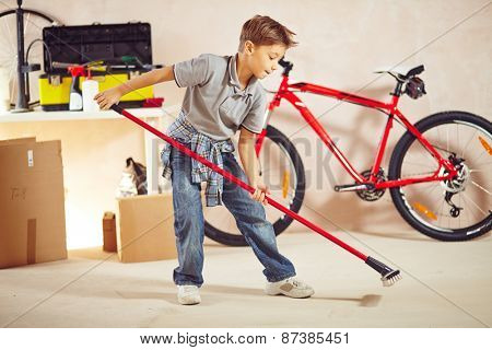 Cute lad doing cleanup in garage