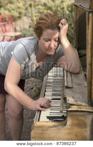 Mature Woman Playing Antique Wooden Piano In Desert Setting