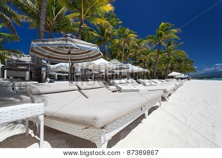 Sun Umbrellas And Beach Beds On Tropical Coastline