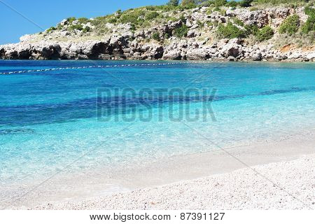 Blue clear water on the beach with a rock