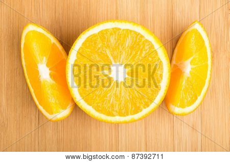 Few Slices Of Orange Lying On Bamboo Table
