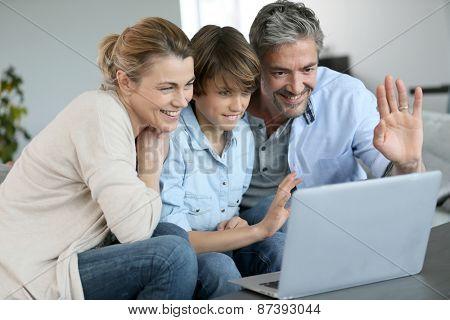 Happy family of three waving at camera during video call