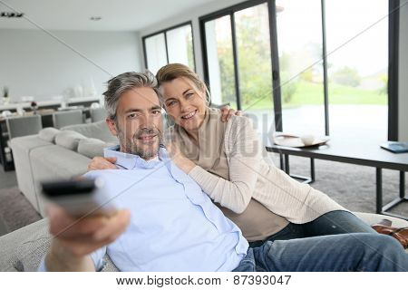 Middle-aged couple in living-room watching television