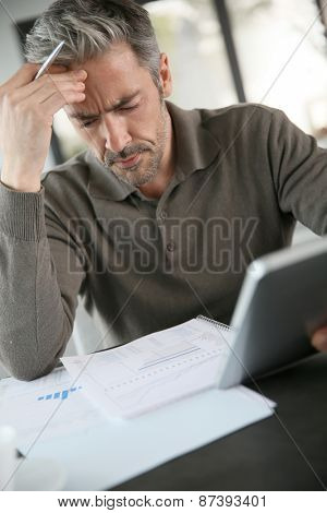 Mature businessman working from home with tablet